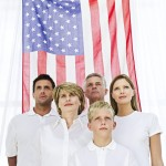 Image of Family standing in front of American flag - Denver Hearing Aids