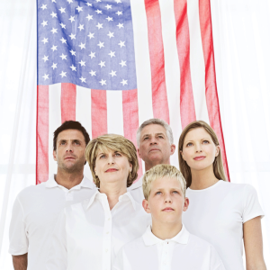 Family-standing-in-front-of-American-flag
