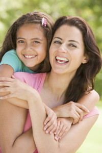 image of woman and young girl embracing outdoors smiling - Free Hearing Test Denver